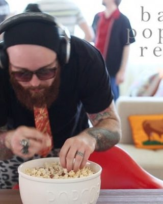 A person sitting at a table with food eating bacon  popcorn