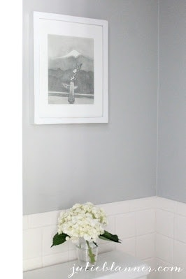 A vase with flowers in front of a wall.
