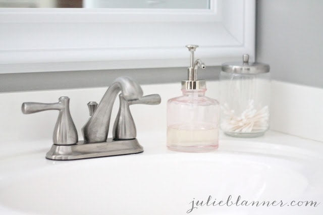 A sink with a pink soap dispenser and a glass container with qtips.
