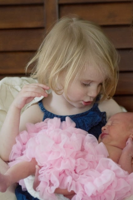 A little girl playing with her newborn baby sister.