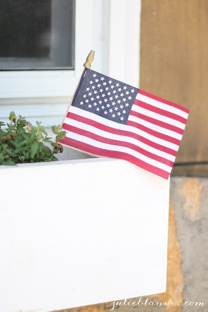 An American Flag sticking out of a small potted plant.