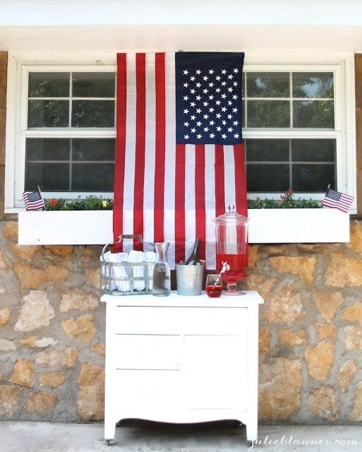 A mini Fourth of July themed bar, with red punch, white and navy striped towels, and an American Flag hanging above it.