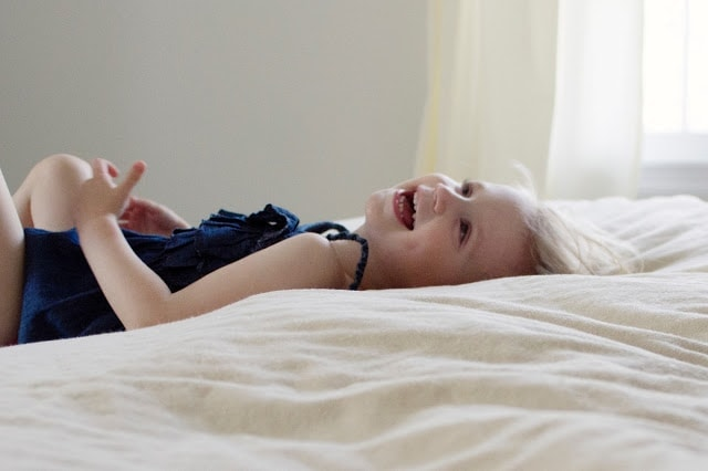 A little girl lying on a bed laughing.