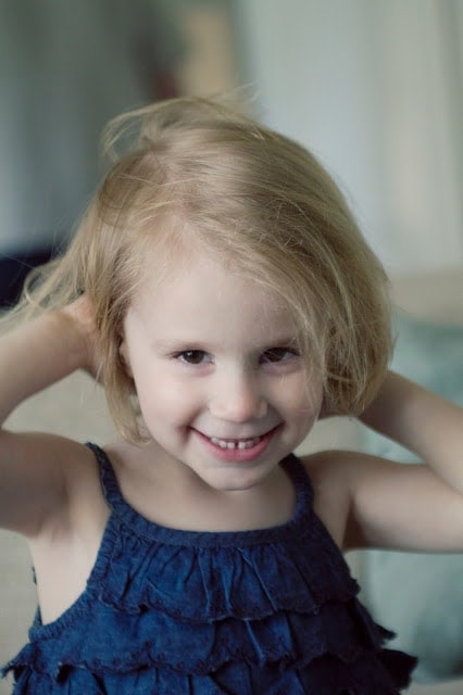A little girl smiling and hitting a pose for the camera.