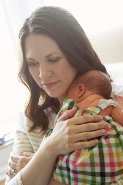 A woman holding her newborn baby girl who is wearing a plaid dress.