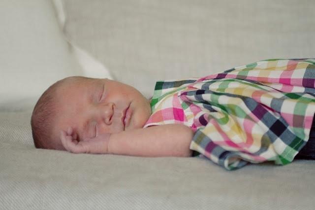 A close up of a newborn baby girl wearing a plaid dress.