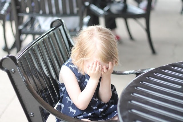 A little girl sitting on a bench, playing peek-a-boo.