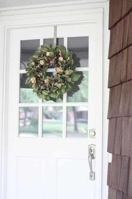 A front door with a window and a wreath.