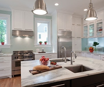 A kitchen with a marble island in the middle.