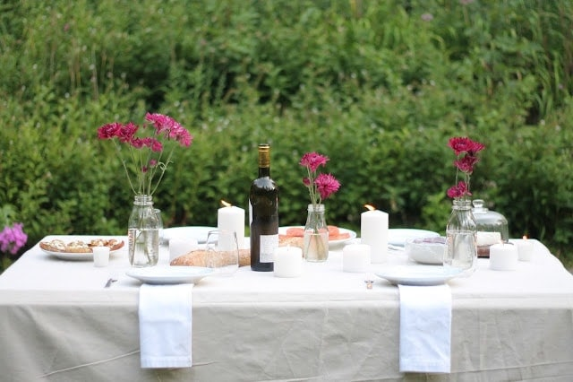 A set table with wine and pink flowers in a mason jar vase.
