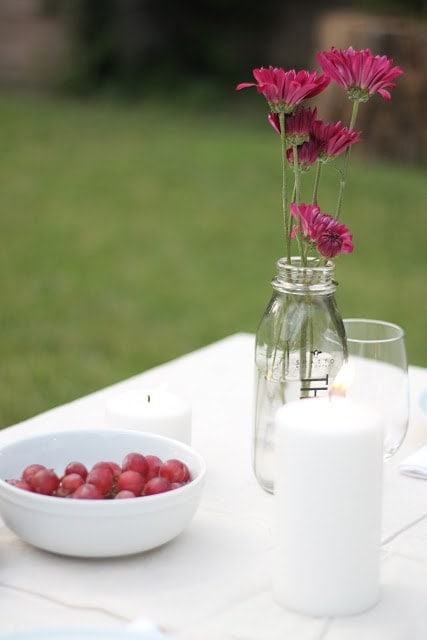 A set table with pink flowers in a mason jar vase. A bowl of grapes to the left.