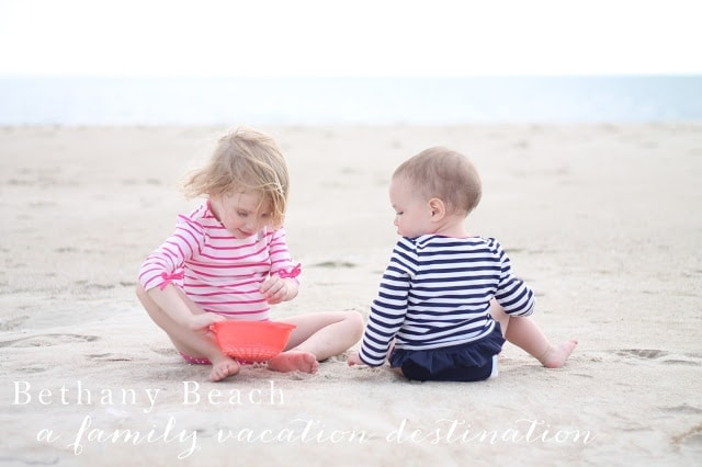 Two little kids playing in the sand at the beach.