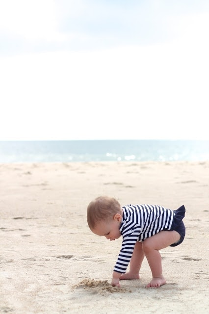 A little kid playing in the sand at the beach.