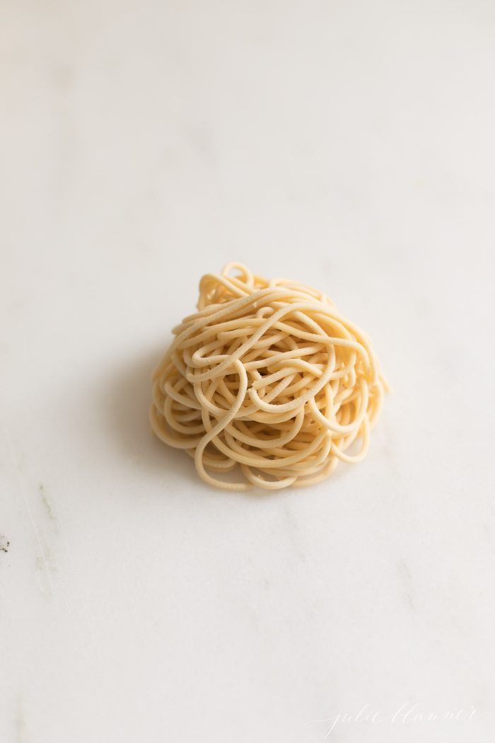 A little pile of homemade egg noodles in spaghetti shape on a marble countertop.