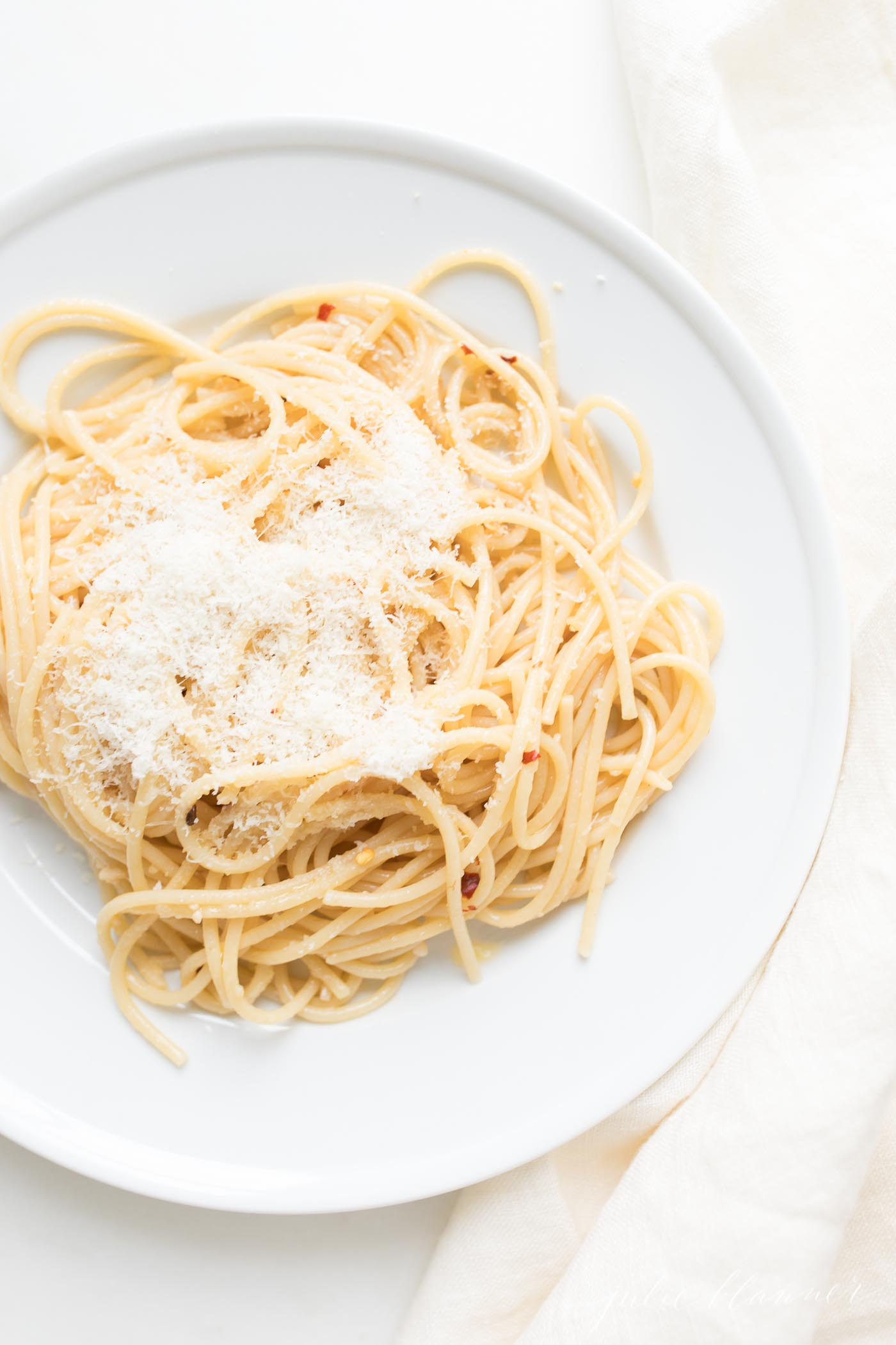 Fresh made pasta on a white plate covered in fresh grated cheese.