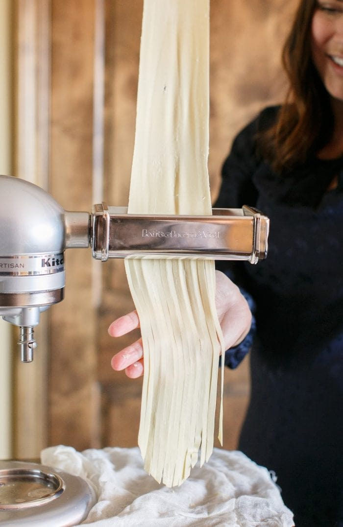 Pasta noodles being cut and made with a Kitchen Aid pasta maker.