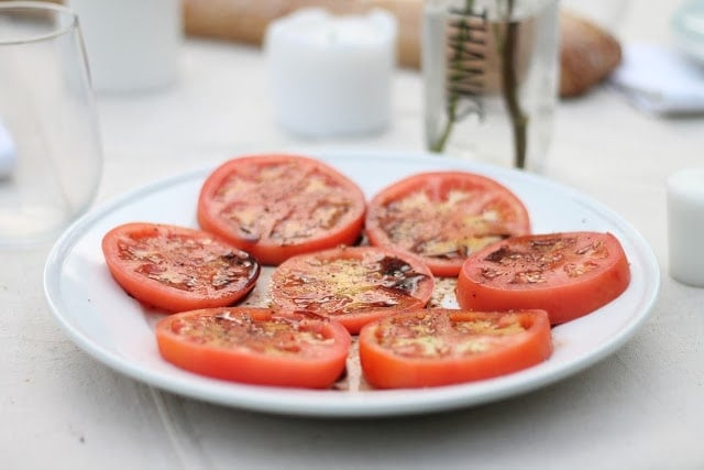 Seasoned tomato appetizers on a white plate with candles in the background.