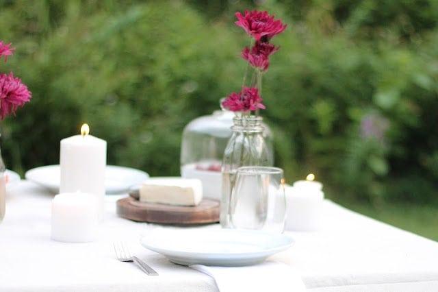 A mason jar vase of pink flowers on a set table.