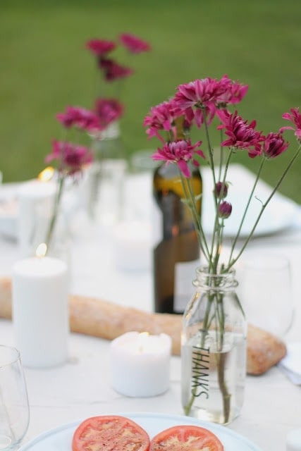 A set table with pink flowers in a mason jar vase.