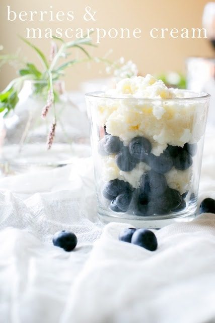 Berries with Mascarpone cream in a white jar, on a white cloth with blueberries and greenery surrounding it.