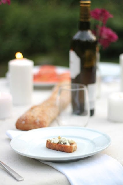 A set table with wine behind a white plate with a bread appetizer.