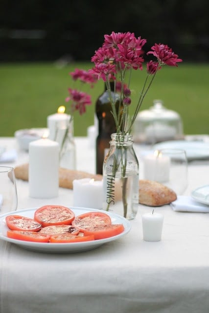 A mason jar vase of pink flowers on a set table, a plate of tomatoes to the left.