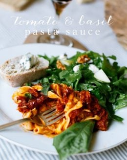 sun dried tomato pasta sauce with basil, salad and bread on white plate with text overlay