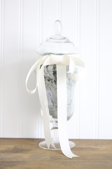 A housewarming gift in a glass container with a white ribbon around it.