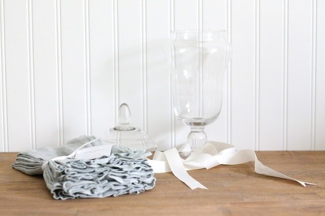 Linen napkins next to a glass container with ribbon on a wood surface.
