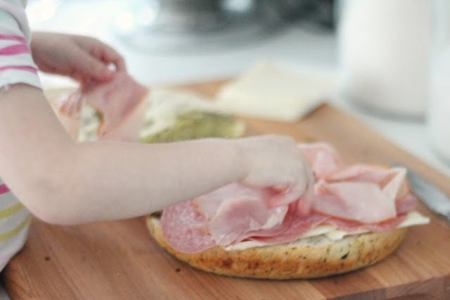 Placing the ham on top of the bread