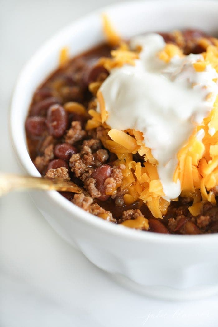 Close up of a spoon in a bowl of chili
