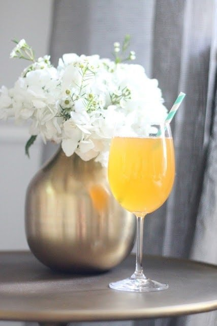 A non-alcoholic bellini with a straw in front of a vase of flowers