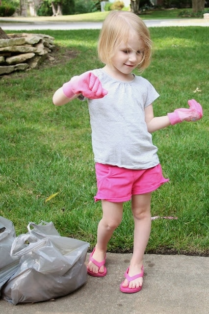 A little girl that is standing in the grass with gardening gloves on