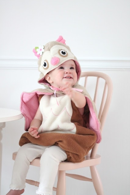 A baby sitting in a chair in a costume