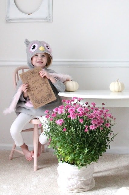 A girl dressed up holding a printable with flowers and pumpkins next to her.