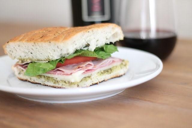 A focaccia sandwich next to a glass of wine