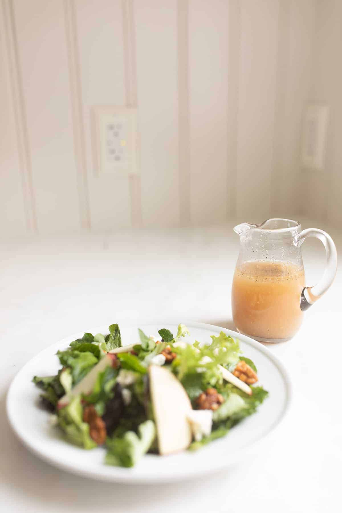 salad with apples next to apple cider vinaigrette in small clear glass pitcher