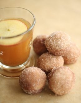apple cider donut holes with apple cider in a glass