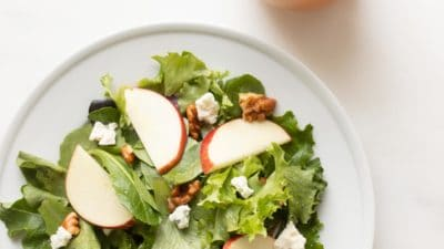 apple cider vinegar salad dressing in a pourable dispenser next to a salad on a plate
