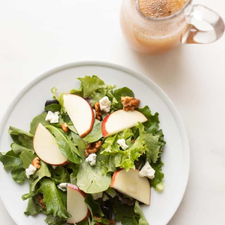Apple cider vinegar dressing in a glass pitcher next to a plate of fresh salad.