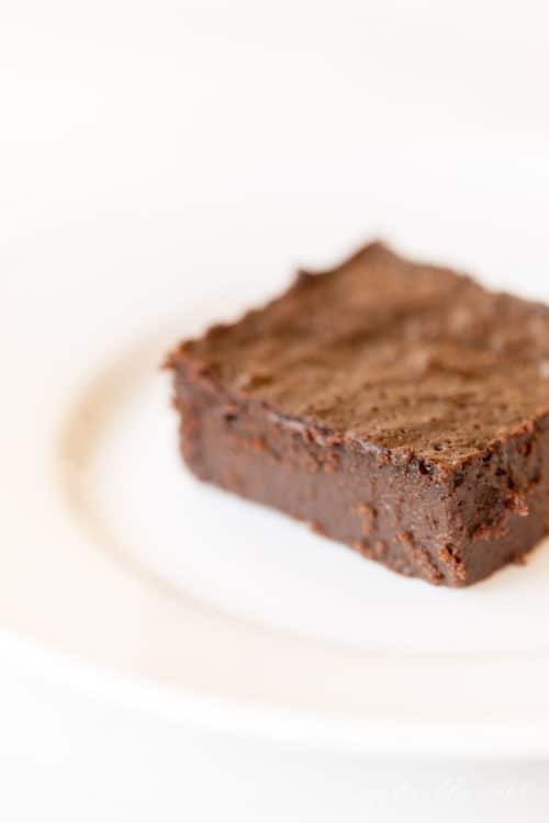 White plate with a slice of flourless brownies.