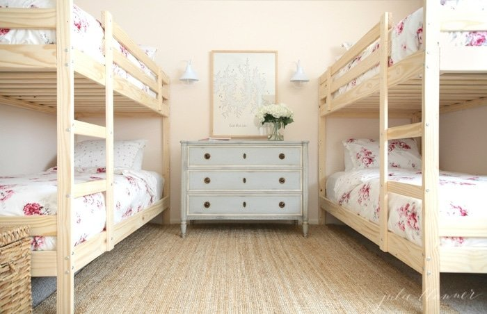 Girls bunk bedroom with wood bunk beds and floral bedding.
