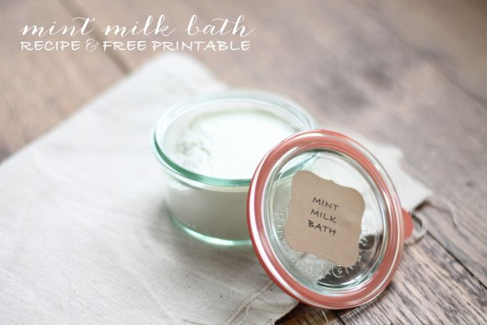 milk bath in a clear glass jar on a wood surface, with a linen towel in background.