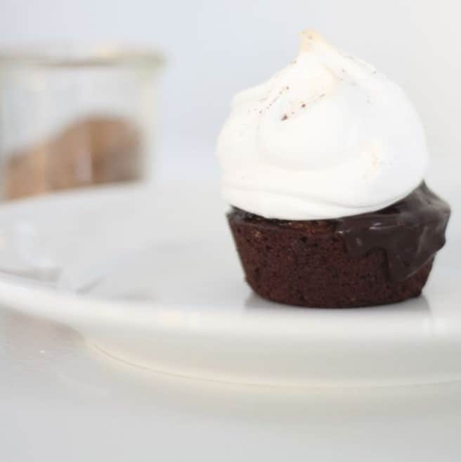 A single serving of a hot chocolate cake topped with meringue on a white plate.