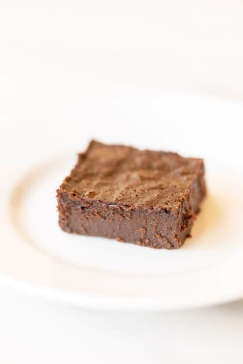 White plate with a single decadent gluten free brownie slice.
