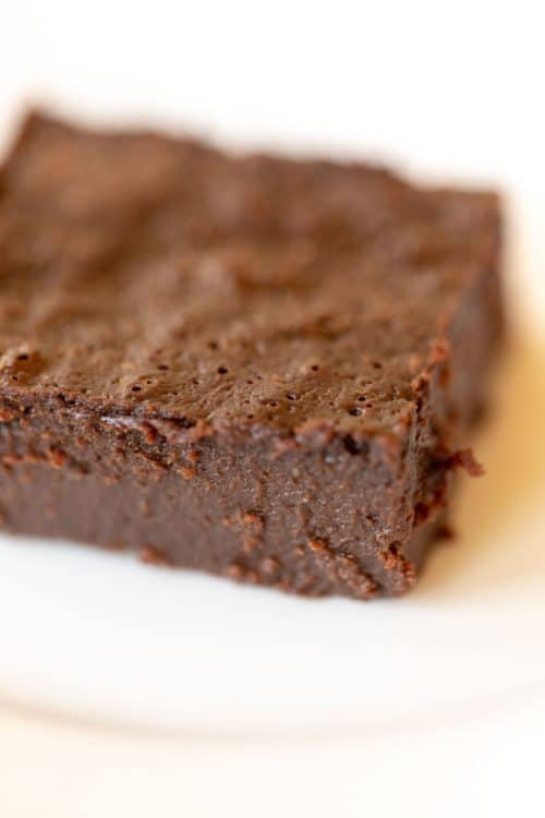 White surface with a single decadent gluten free brownie slice.