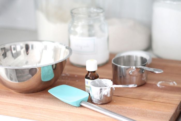 milk bath recipe ingredients in silver measuring cups on a wooden surface.