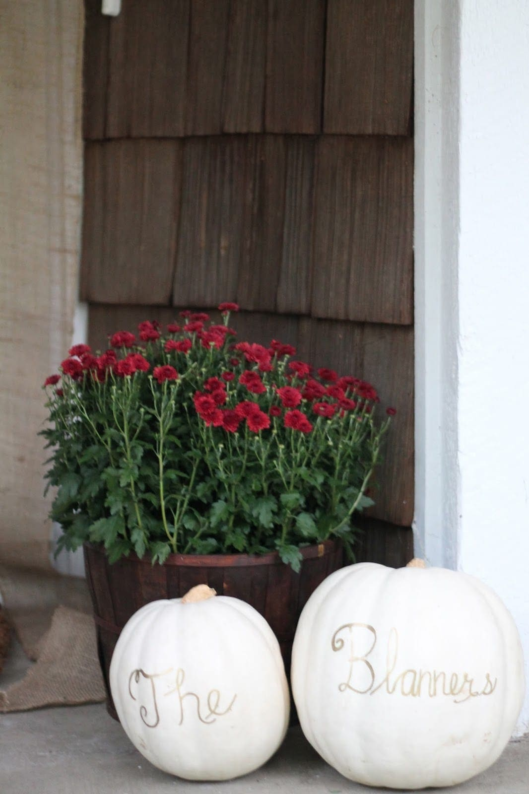 Bushel filled with mums and monogrammed pumpkins on the front porch