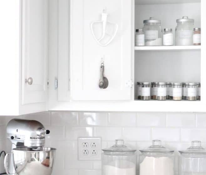 baking supplies in a cabinet and on counter with kitchenaid mixer on counter and attachments hanging on cabinet door