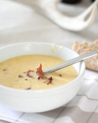 bacon and cheese soup in white bowl with silver spoon